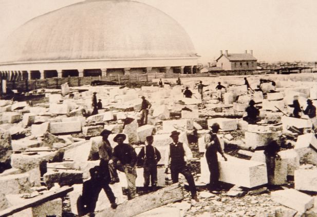 An old photograph showing workmen walking among large granite blocks on the piece of land next to the newly constructed Salt Lake Tabernacle.