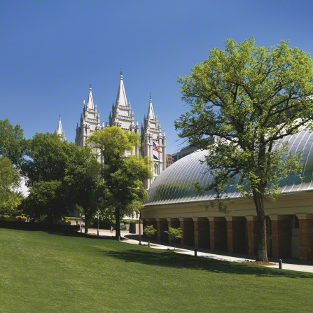 A large grass lawn next to the Tabernacle, with the Salt Lake Temple spires rising above the trees in the background.