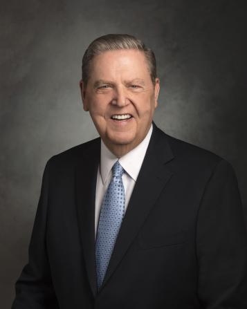 A portrait of Jeffrey R. Holland wearing a black suit and a light blue tie.