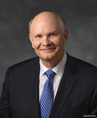 A portrait of Dale G. Renlund wearing a dark suit and blue tie in front of a gray background.