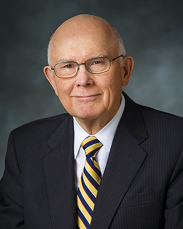 A portrait of Elder Dallin H. Oaks, who is wearing a black pinstriped suit and a yellow and blue striped tie, in front of a blue background.
