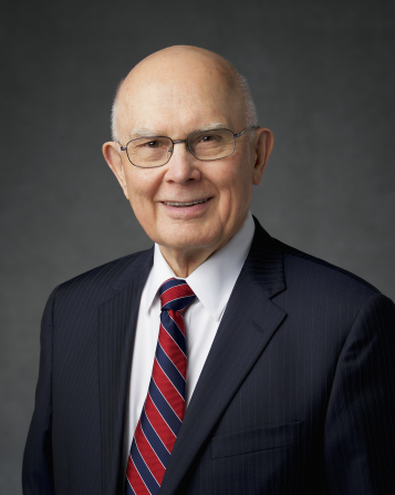 A portrait of President Dallin H. Oaks wearing a black pin-striped suit and a tie with red and blue stripes.