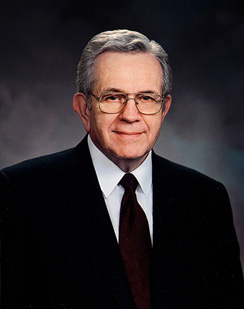 A portrait of President Boyd K. Packer, who is wearing a black suit and a maroon tie, in front of a gray background.