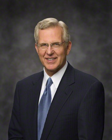 A portrait of D. Todd Christofferson, who is wearing a blue suit with a blue and white tie, in front of a gray background.