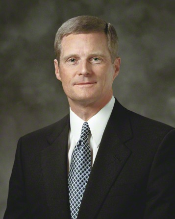 A portrait of Elder David A. Bednar, who is wearing a black suit with a black and white geometric tie, in front of a gray background.