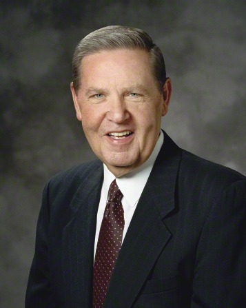 A portrait of Elder Jeffrey R. Holland, who is wearing a black pinstriped suit and a maroon tie with white dots, in front of a gray background.