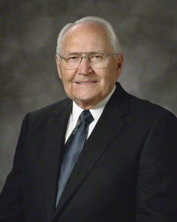 A portrait of Elder L. Tom Perry, who is wearing a black suit and a blue tie, in front of a gray background.