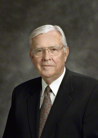 A portrait of Elder M. Russell Ballard, who is wearing a black suit and a red and blue patterned tie, in front of a gray background.