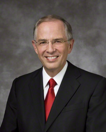 A portrait of Elder Neil L. Andersen, who is wearing a black suit and a solid red tie, in front of a gray background.