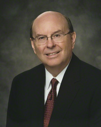A portrait of Elder Quentin L. Cook, who is wearing a black suit and a maroon and white tie, sitting in front of a gray background.