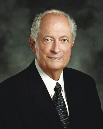 A portrait of Elder Robert D. Hales, who is wearing a black suit and black tie with white dots, in front of a blue background.