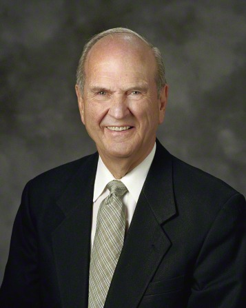 A portrait of President Russell M. Nelson, who is wearing a black suit and a green tie, in front of a gray background.