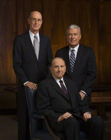 A portrait of the First Presidency, with President Monson in a chair, President Eyring standing behind him, and President Uchtdorf seated on a bench.