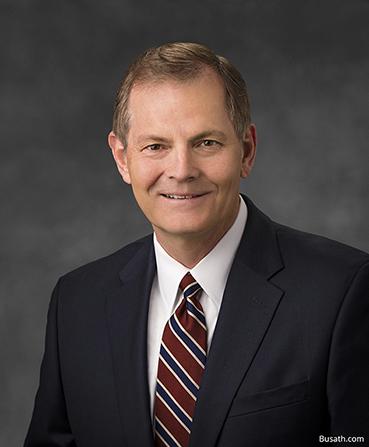 A portrait of Elder Gary E. Stevenson wearing a dark suit and striped tie in front of a gray background.