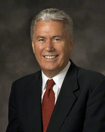 A formal portrait of President Dieter F. Uchtdorf, who is wearing a black suit and a red tie with white dots, in front of a gray background.