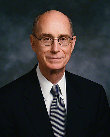 A formal portrait of President Henry B. Eyring, who is wearing a black suit and a black and white striped tie, in front of a blue background.