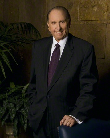 A portrait of President Thomas S. Monson in a black suit and purple tie, standing with his arm resting on a blue chair and with green plants to the left.