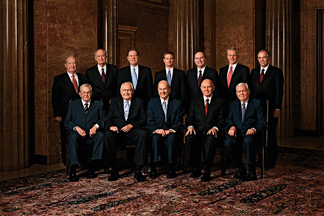 A portrait of the Quorum of the Twelve Apostles, five of them sitting in a row of chairs and the remaining seven standing behind them.