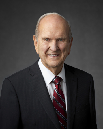 A portrait of Russell M. Nelson wearing a black suit and a red and blue striped tie.
