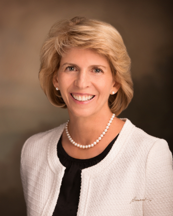 A portrait of Sister Carol F. McConkie, who is wearing a white sweater, in front of a brown background.
