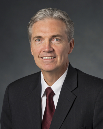 A portrait of Brother Devin G. Durrant, who is wearing a dark suit and a red tie, in front of a grey background.