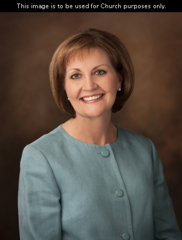 A portrait of Sister Linda K. Burton, who is wearing a turquoise jacket, in front of a brown background.