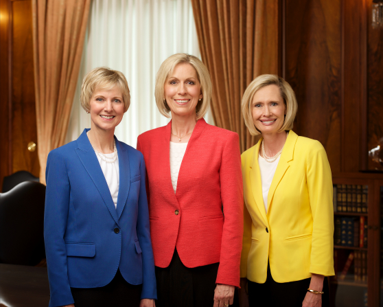 An indoor semiformal group portrait of Joy D. Jones, Jean B. Bingham, and Bonnie H. Cordon wearing colored blazers.