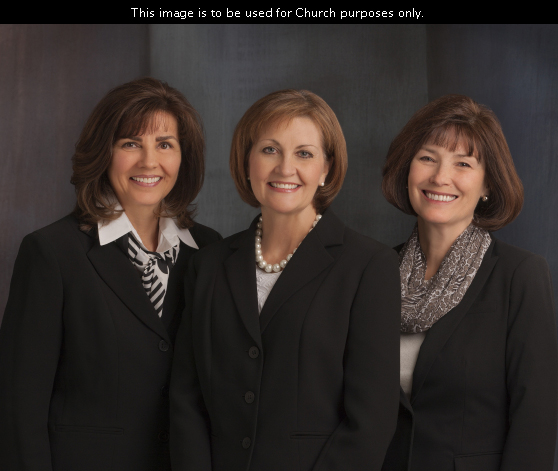 A portrait of the three members of the Relief Society general presidency wearing black blazers and standing in a row in front of a blue background.