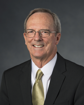 A portrait of Brother Tad R. Callister, who is wearing a black suit and a gold tie, in front of a gray background.