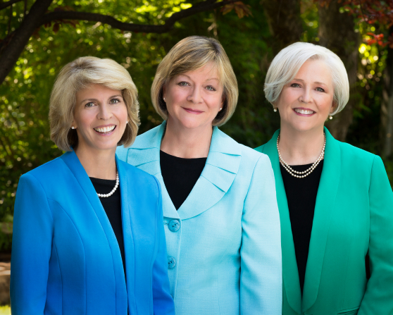A portrait of the Young Women general presidency in pastel-colored jackets, standing outside in front of green trees.