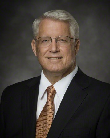 A portrait of Bishop Dean M. Davies, who is wearing a black suit and an orange and black tie, in front of a gray background.
