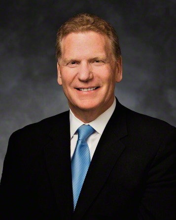 A portrait of Elder Craig C. Christensen, who is wearing a dark suit with a blue tie, in front of a gray background.