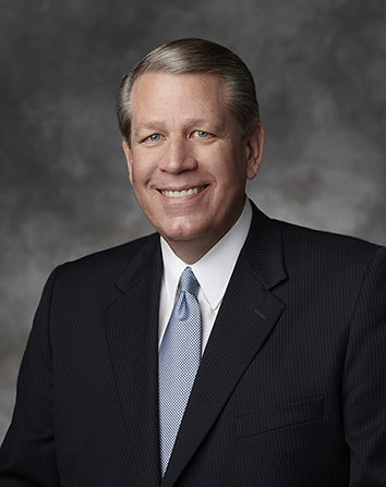 A portrait of Elder Donald L. Hallstrom, who is wearing a dark pinstriped suit with a blue tie, in front of a gray background.