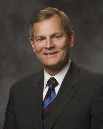 A portrait of Elder Gary E. Stevenson, who is wearing a dark gray suit with a blue striped tie, in front of a gray background.