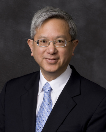 A portrait of Elder Gerrit W. Gong wearing a black suit and a light blue tie in front of a gray background.