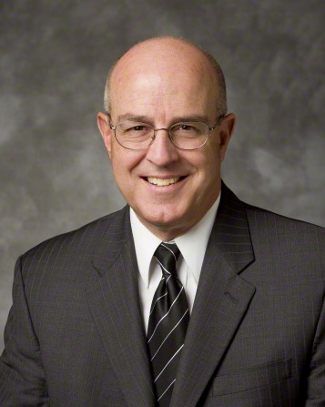 A portrait of Elder L. Whitney Clayton, who is wearing a gray suit and black tie with white stripes, in front of a gray background.