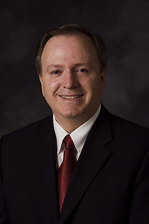 A portrait of Elder Lynn G. Robbins, who is wearing a dark suit and a red tie, in front of a dark gray background.