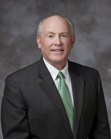 A portrait of Elder Richard J. Maynes, who is wearing a dark gray suit and a green tie, in front of a gray background.