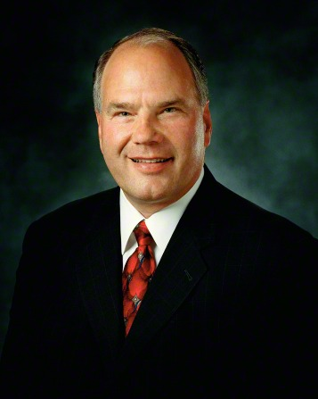 A portrait of Elder Ronald A. Rasband, who is wearing a dark suit and red tie, in front of a blue background.