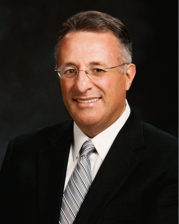 A portrait of Elder Ulisses Soares, who is wearing a black suit with a silver tie, in front of a dark gray background.