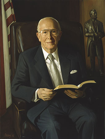 A painted portrait by Knud Edsberg of President Ezra Taft Benson in a blue suit and silver tie, sitting in a brown chair, with an American flag and a statue of Joseph Smith in the background.