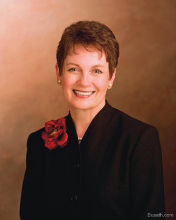 A photograph of Cheryl C. Lant against a brown background, wearing a black blazer with a red rose pin.