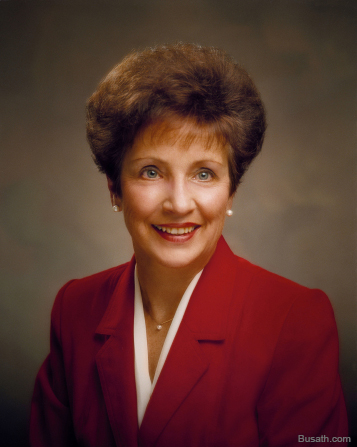 A photograph of Dwan Jacobsen Young sitting against a dark gray background, wearing a red blazer with a white blouse.