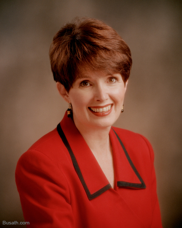 A photograph of Michaelene Packer Grassli against a brown background, wearing a red blazer.