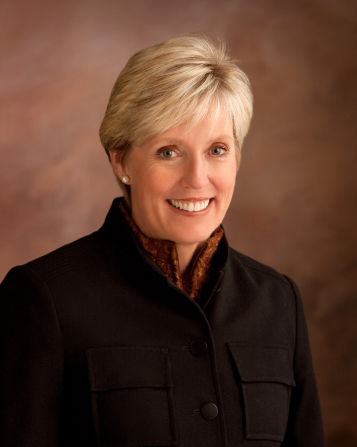 A photograph of Rosemary M. Wixom against a brown background, wearing a black blazer.