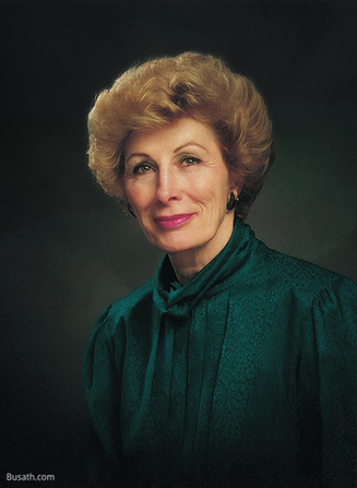 A photograph of Elaine Low Jack against a gray background, wearing a dark green blouse.