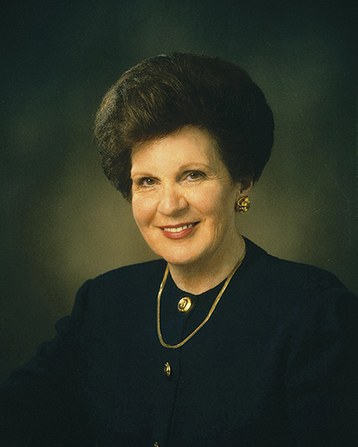A photograph of Mary Ellen Wood Smoot against a gray background, wearing a gold necklace and a black dress with gold buttons down the front.