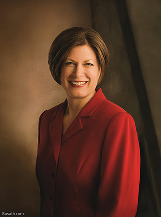 A photograph of Julie Bangerter Beck against a brown background, wearing a red blazer.