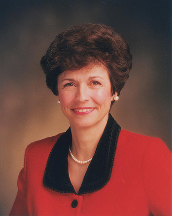 A photograph of Margaret Dyreng Nadauld against a brown background, wearing a red blazer with a black collar.