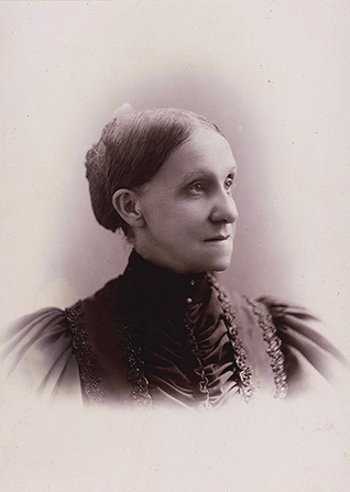 A photograph of Elmina Shepard Taylor wearing a high-collared black dress. The image is in black and white.
